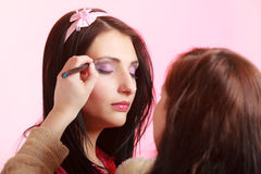 Makeup artist stylist applying eyeshadow on eyelid of woman Royalty Free Stock Image