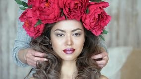 Makeup artist stylist works with model. Women`s hands straighten out the long dark curly hair of the model. 4K stock video