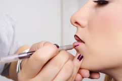 Makeup artist tracing red contour on the lips Stock Photos