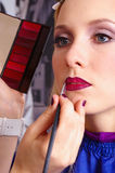 Makeup artist tracing red lipstick Stock Images