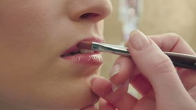 Makeup artist uses brush to apply lip gloss to model lips stock footage