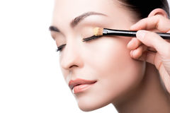 Makeup artist using brush to apply eye shadow on face of woman. On white bakcground Royalty Free Stock Photo