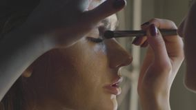 Makeup artist using cosmetics brush for applying eye shadow on eyelid. Makeup face to beautiful woman. Close up waterproof makeup for fashion model stock footage