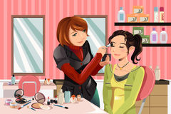 Makeup artist at work. A vector illustration of a makeup artist working on a client at a beauty salon Stock Images