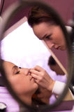 Makeup artist at work. Makeup artist applying cosmetics to face of young woman, reflected in glass mirror Stock Image