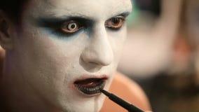 Makeup artist at work applying halloween makeup. Makeup artist at work applying scary halloween makeup stock video footage