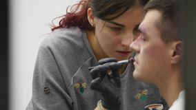 Makeup artist at work applying special effects makeup.  stock footage