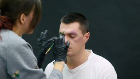 Makeup artist at work applying special effects makeup.  stock video