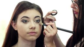 Makeup artist at work with a client in a beauty salon doing make-up. stock footage