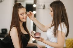 Makeup artist work in her beauty studio. Woman applying by professional make up master. Beautiful make up artist make a stock photos