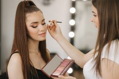 Makeup artist work in her beauty studio. Woman applying by professional make up master. Beautiful make up artist make a royalty free stock image