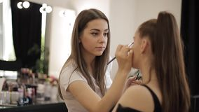 Makeup artist work in her beauty studio. Woman applying by professional make up master. Beautiful make up artist make a stock video