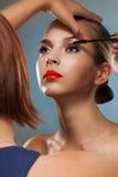 Makeup artist at work. Make up artist at work, correcting eye lashes preparing motel to beauty photo session Royalty Free Stock Photo