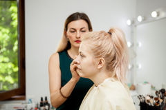 Makeup artist at the work place applying make up to a model. Makeup artist at the work place applying make up to a young beautiful model Royalty Free Stock Photos