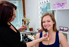 Makeup artist at work in salon. Makeup artist at work on attractive women in salon Royalty Free Stock Image