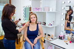 Makeup artist at work in salon. Makeup artist at work on attractive women in salon Stock Images
