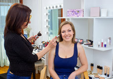 Makeup artist at work in salon. Makeup artist at work on attractive women in salon Royalty Free Stock Images