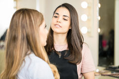 Makeup artist at work in a salon. Attractive young Hispanic makeup artist putting some makeup on a client in her beauty studio Stock Photo