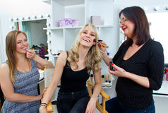 Makeup artist at work in salon. Makeup artist at work on a women model in beauty salon Royalty Free Stock Image