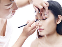 Makeup artist working on a female asian model Royalty Free Stock Image