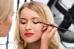 Makeup artist working with models eye makeup. Eye makeup. Female makeup artist is busy applying professional eye shadows stock photos