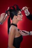 Makeup artists working on devil woman Stock Photos