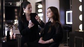 Makeup artysta - brunetki kobieta w czarnym stosuje konturu i głównej atrakcji makeup na cheekbones piękna dziewczyna Twarz zbiory wideo