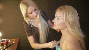 Makeup artysta robi dziewczynie pięknemu makeup przed znacząco wydarzeniem kobieta stosuje kosmetyka z muśnięciem uzupełniał zdjęcie wideo