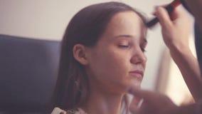 Makeup artysta robi młodej kobiecie pięknemu makeup przed znacząco wydarzeniem Makeup Stosować 1920x1080 zbiory wideo