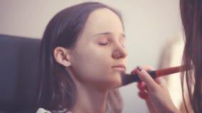 Makeup artysta robi młodej kobiecie pięknemu makeup przed znacząco wydarzeniem Makeup Stosować 1920x1080 zdjęcie wideo