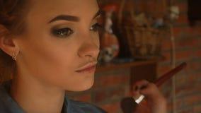 Makeup artysta rozdaje na młodym policzka highlighter zbiory wideo