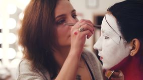 Makeup artysta rysuje linię na wzorcowej ` s twarzy zbiory