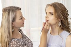 Makeup artysta stawia uzupełnia na dziewczyna modelu ślubny makeup, wieczór makeup, naturalny makeup makijażu artysta maluje warg zdjęcia stock