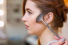 Makeup artysta stosować z szczotkarskim rumienem na dziewczyny ` s twarzy, wnioskuje dziennego makijaż Fotografia Stock