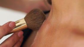 Makeup artysta stosuje highlighter proszek na decollete i szyję młoda kobieta Zamyka w górę visagiste stosuje makeup dalej zbiory wideo