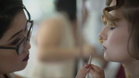 Makeup artysta stosuje pomadkę wargi posadzona kobieta indoors zbiory wideo
