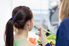 Makeup artysta stosuje makeup z muśnięciem na twarzy kobieta obrazy stock