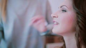 Makeup artysta stosuje z muśnięciem, use dekoracyjni kosmetyki Zakończenie widok młody atrakcyjny kobiety czekanie dla makijażu zbiory wideo
