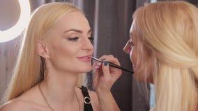 Makeup artysta używa muśnięcie dla podaniowej pomadki na wargi pięknej kobiecie Zamyka w górę podaniowej wargi glosy na wargach zbiory wideo