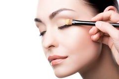 Makeup artysta używa muśnięcie stosować oko cień na twarzy kobieta zdjęcie royalty free