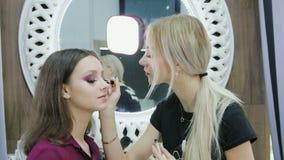 Makeup artysta wykonuje rzęsy kolorystykę na pięknym modelu w piękno salonie zdjęcie wideo