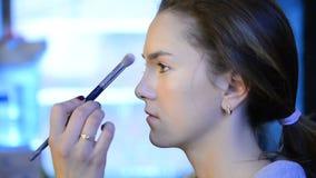 Makeup artysty farb proszek na brown długowłosym modelu w studiu zbiory