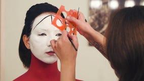 Makeup artysty początek rysować linię na wzorcowej ` s twarzy zbiory