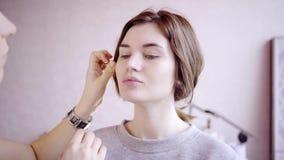 Makeup artysty spojrzenia przy wzorcowym ` s stawiają czoło zdjęcie wideo