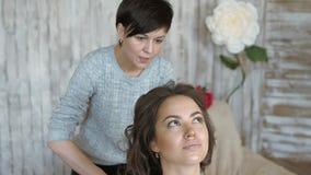 Makeup artysty stylisty pracy z modelem fryzjer robi włosianemu tytułowaniu model zbiory
