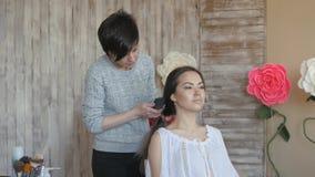 Makeup artysty stylisty pracy z modelem fryzjer robi włosianemu tytułowaniu model Kobieta czesze długiego zmrok zdjęcie wideo