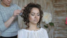 Makeup artysty stylisty pracy z modelem fryzjer robi włosianemu tytułowaniu model włosiana klamerka trzyma włosianych kędziory zbiory wideo