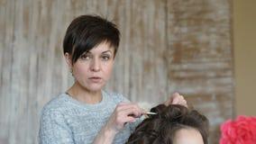 Makeup artysty stylisty pracy z modelem fryzjer robi włosianemu tytułowaniu model włosiana klamerka trzyma włosianych kędziory zdjęcie wideo