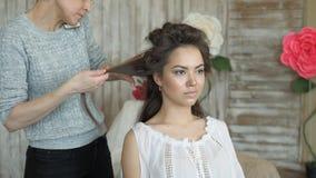 Makeup artysty stylisty pracy z modelem fryzjer robi włosianemu tytułowaniu model włosiana klamerka trzyma włosianych kędziory zbiory