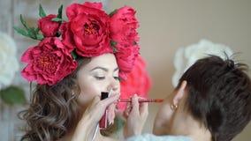 Makeup artysty stylisty pracy z modelem stylista rysuje kontur wzorcowe ` s wargi z czerwonym ołówkiem zbiory wideo